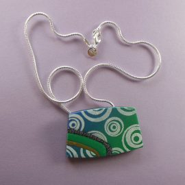 S342 This roughly rectangular pendant shades from blue to green with a white design. It has inset stripes of black and silver, green and gold. It is suspended on a 46cm (18 inches) sterling silver snake chain.